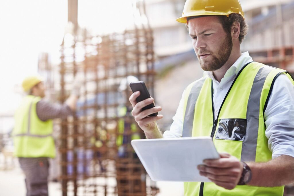 Construction field worker reviewing original documents and mobile updates.