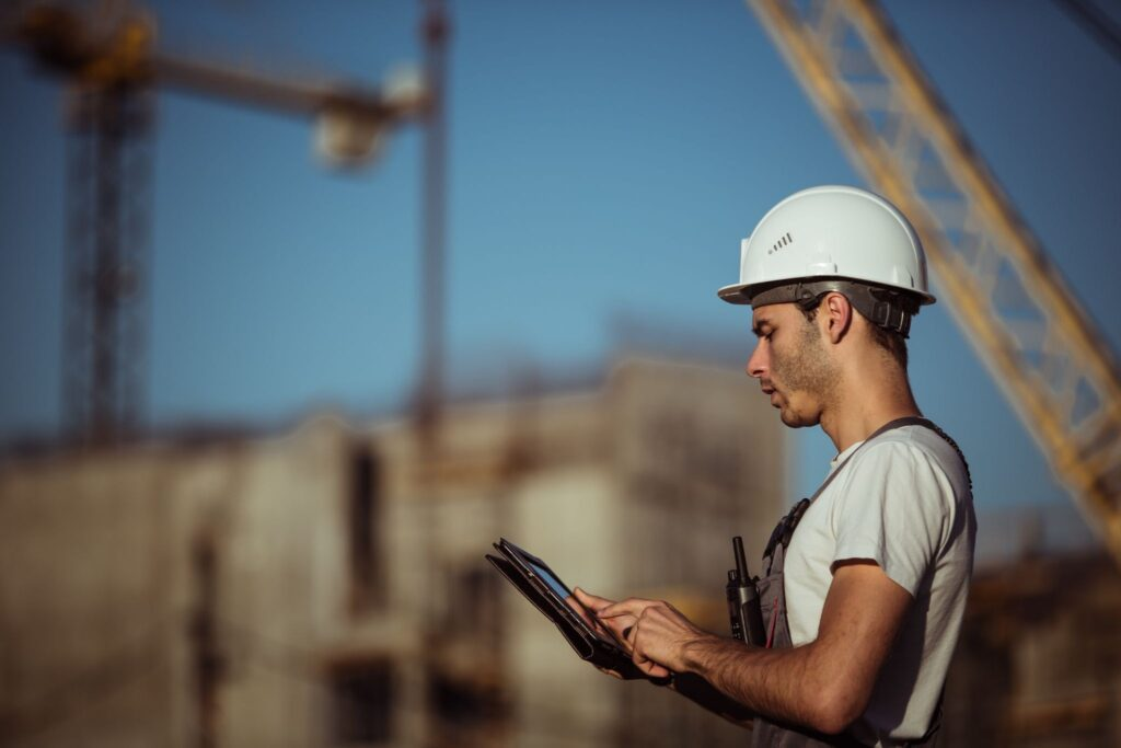 Construction field worker reviewing change order statuses on a mobile device.
